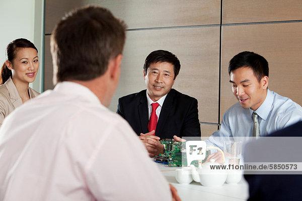 Geschäftsleute diskutieren im Meeting über die Platine