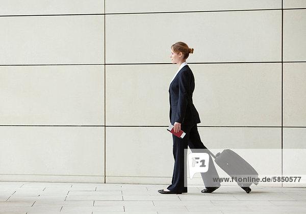 Geschäftsfrau beim Wandern und Ziehen von Gepäck