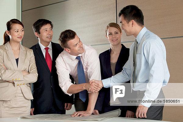 Multirassische Geschäftsleute schütteln die Hand über die Blaupause
