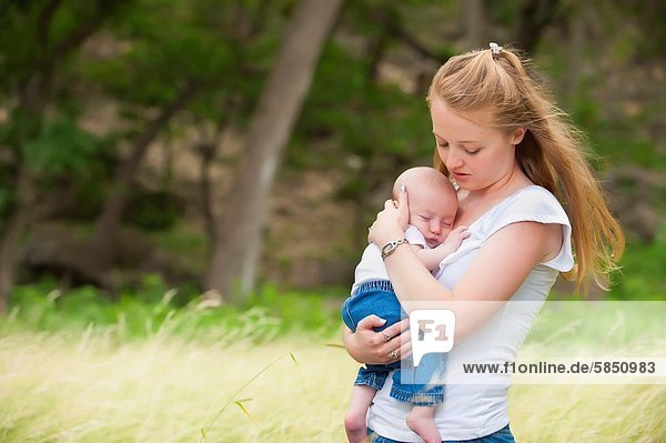 A young happy mother holding her four months old baby boy in a natural environment