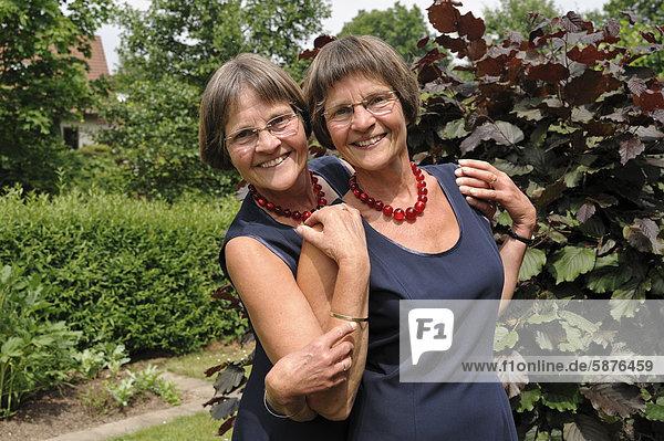 Zwei rüstige Zwillingsschwestern  gleich gekleidet  Portrait
