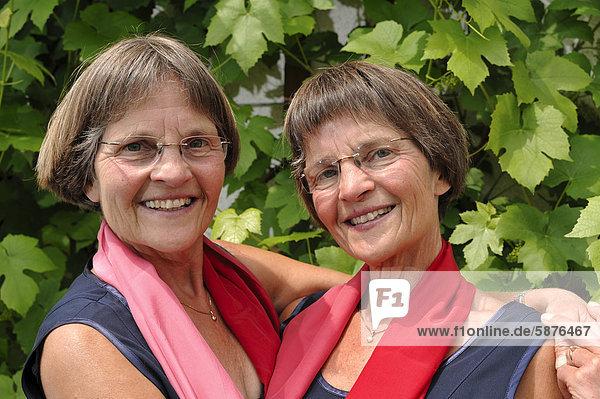 Lusty twin sisters  dressed alike in red scarves  portrait