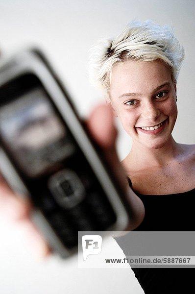 Portrait einer jungen Frau  die ein Mobiltelefon