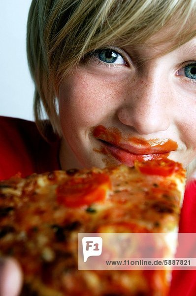 Close_up of a boy holding a pizza