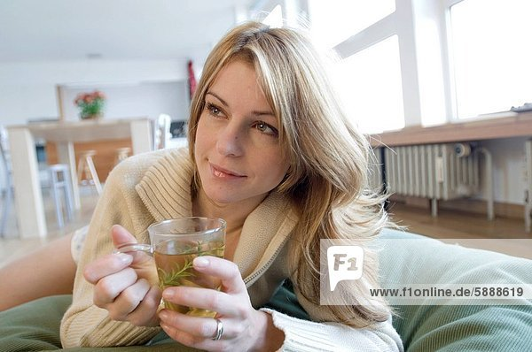 Close_up of a young woman holding a cup of herbal tea