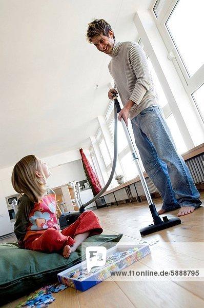 sitzend  nebeneinander  neben  Seite an Seite  Boden  Fußboden  Fußböden  Menschlicher Vater  Kopfkissen  Staubsauger  Tochter