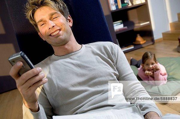 Handy  hinter  liegend  liegen  liegt  liegendes  liegender  liegende  daliegen  Menschlicher Vater  halten  Kopfkissen  Kurznachricht  Tochter