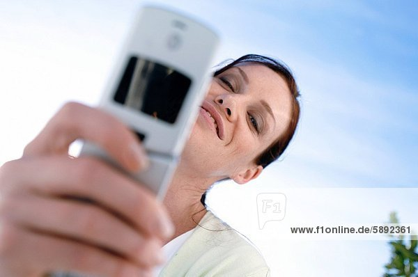 Low angle view of a young woman smiling and holding a mobile phone