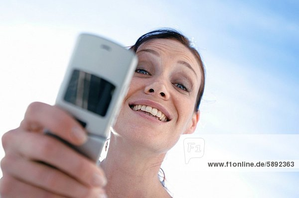Portrait of a young woman smiling and holding a mobile phone