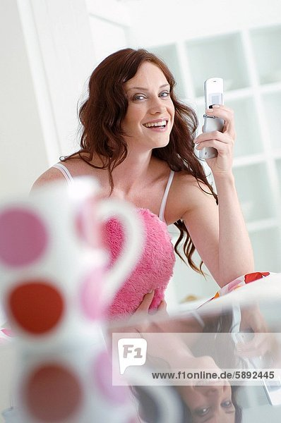 Portrait of a young woman holding a mobile phone and smiling