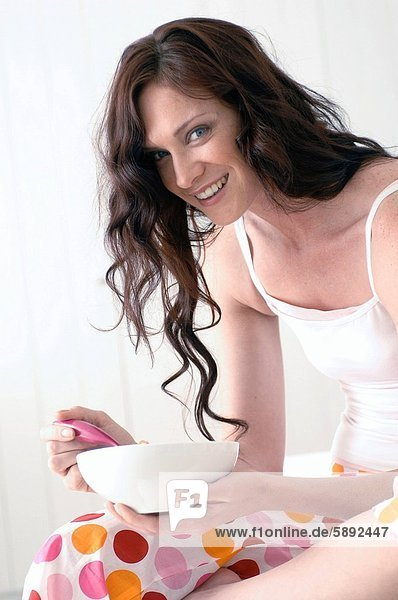 Portrait of a young woman holding a bowl and smiling
