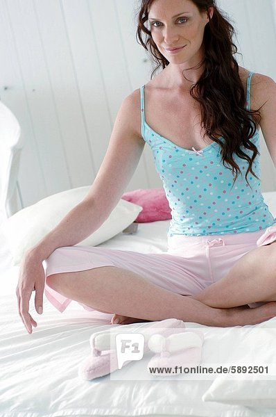 Portrait of a mid adult woman doing yoga on the bed
