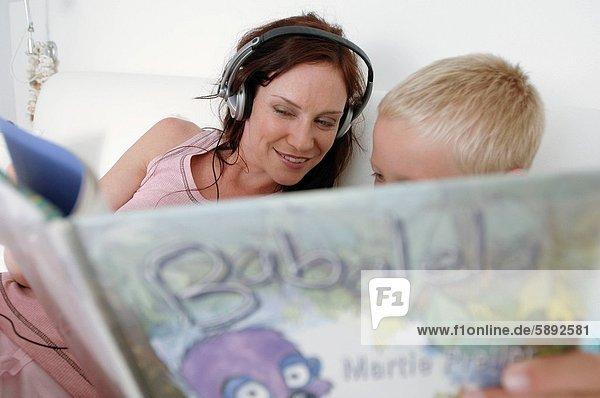 Frau  zuhören  Buch  Sohn  Musik  Mittelpunkt  Taschenbuch  Erwachsener  vorlesen