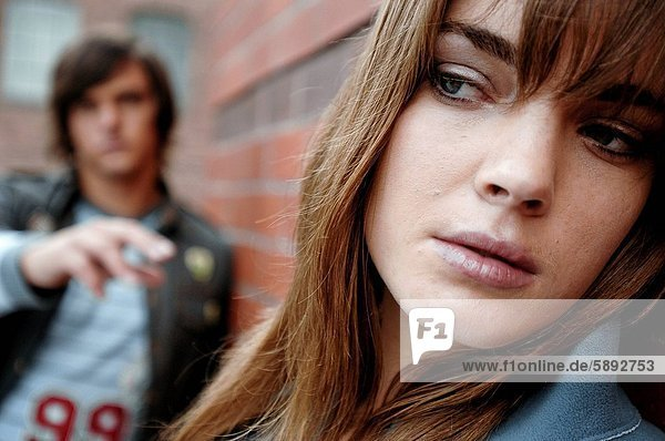 Close_up of a young woman looking serious with a young man standing in the background
