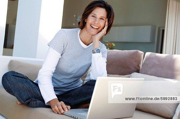 Portrait einer Reifen Frau sitzt auf einer Couch und lächelnd