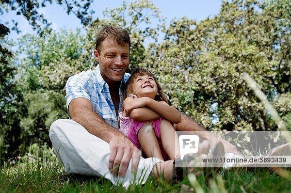 sitzend  lächeln  Menschlicher Vater  Garten  Mädchen