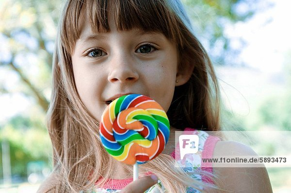 Portrait of a girl holding a lollipop and smirking