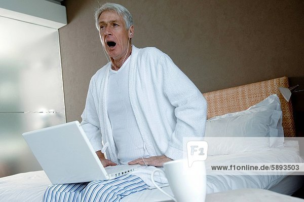 Senior man sitting on the bed with a laptop on his lap
