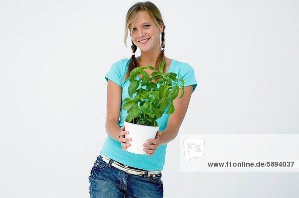Portrait of a junge Frau hält eine Topfpflanze