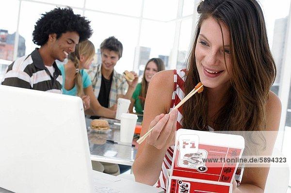 sitzend  Frau  Freundschaft  Notebook  Eßstäbchen  Hintergrund  frontal  jung  essen  essend  isst