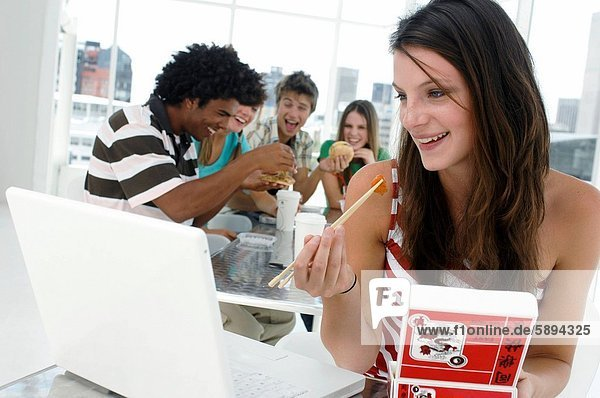 Close_up of a young woman sitting in front of a laptop and eating with chopsticks with her friends sitting in the background