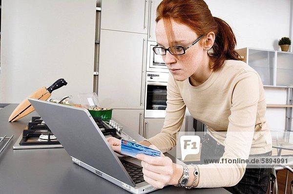 Mitte erwachsen frau benutze ein Laptop und eine Kreditkarte hält