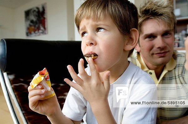 Close_up of a boy eating a chocolate bar with his father sitting behind him