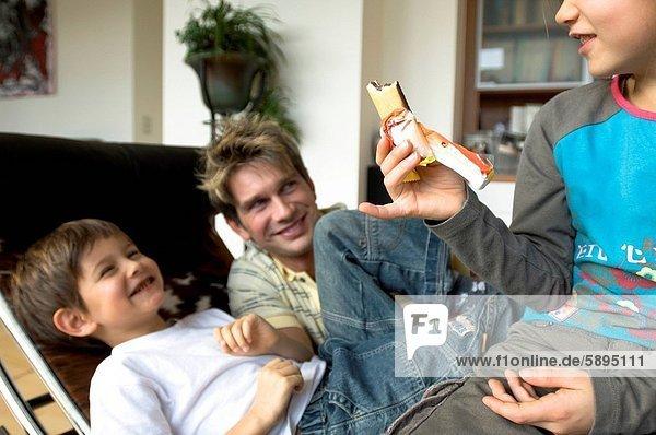 lächeln  Bruder  Menschlicher Vater  halten  Schokolade  Mädchen