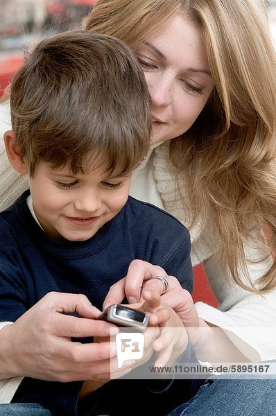 Close_up of a mother and her son using a mobile phone