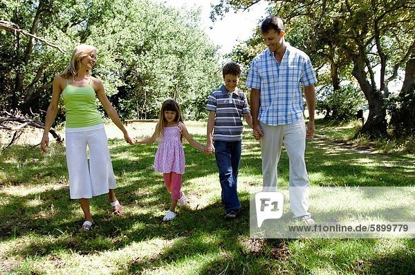 Mid adult couple walking with their two children in a park