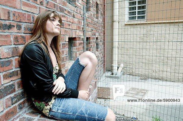 angelehnt  Frau  Wand  Ziegelstein  denken  jung