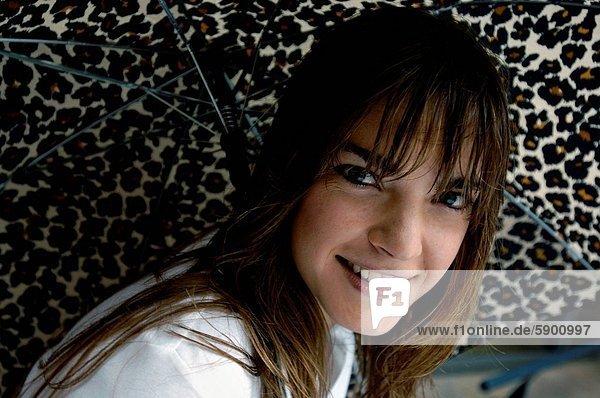 Portrait einer jungen Frau hält einen Regenschirm und lächelnd