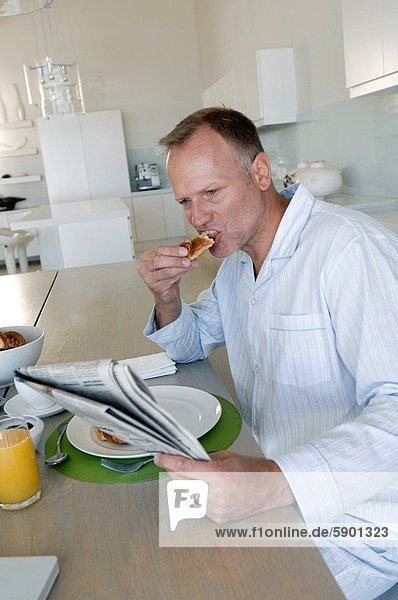 Mann  reifer Erwachsene  reife Erwachsene  Frühstück  Zeitung  vorlesen