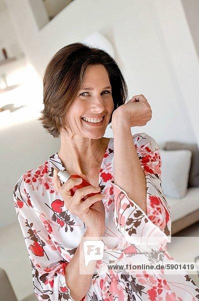 Frau  lächeln  halten  reifer Erwachsene  reife Erwachsene  Parfüm  Flasche