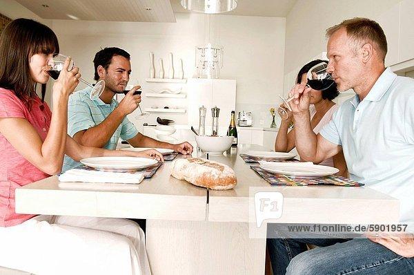 sitzend am Tisch essen Wein reifer Erwachsene reife Erwachsene jung trinken Tisch
