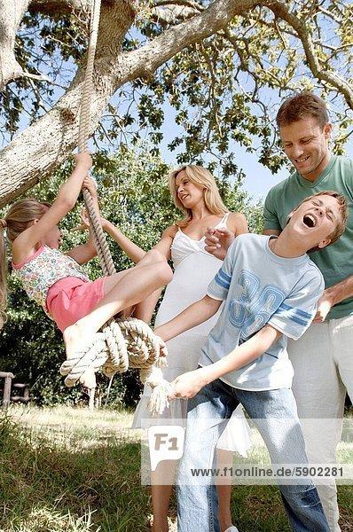schaukeln  schaukelnd  schaukelt  schwingen  schwingt schwingend  lächeln  Junge - Person  Schwester  Seil  Tau  Menschliche Eltern  Schaukel