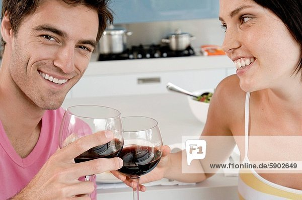 Close_up of a young couple toasting with wine glasses at the kitchen counter
