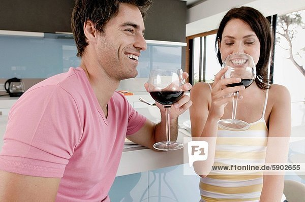 Close_up of a young couple holding glasses of red wine and smiling