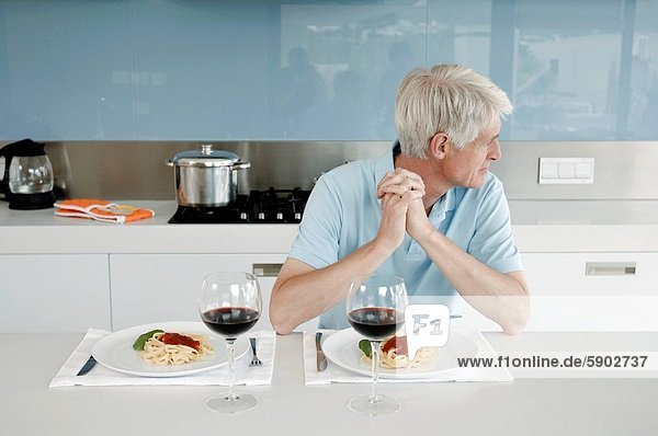 sitzend  Senior  Senioren  Mann  Küche  festhalten  Tresen