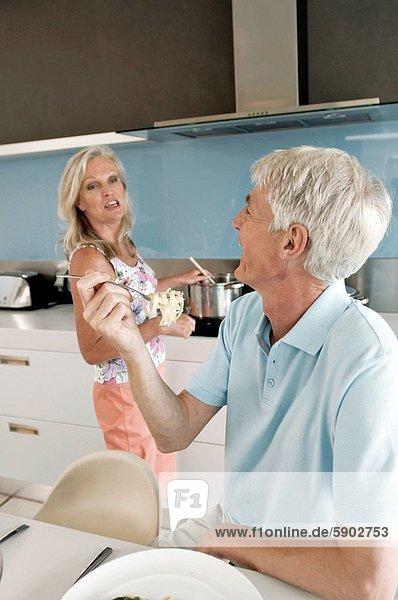 Senior  Senioren  kochen  Frau  Mann  Hintergrund  Ravioli  Fettuccine  Gabel  essen  essend  isst