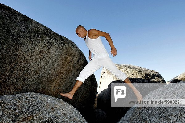 Low angle view of a mid adult man leaping on boulders
