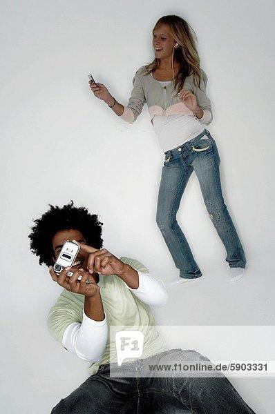 Handy  hinter  Frau  Mann  zuhören  Fotografie  nehmen  Spiel  Kurznachricht  jung  MP3-Player  MP3 Spieler  MP3 Player  MP3-Spieler