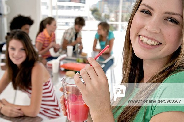 Close_up of a young woman holding a glass of juice and smiling