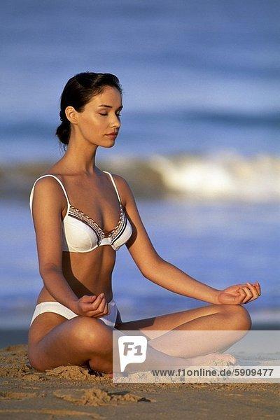 Junge Frau meditieren am Strand