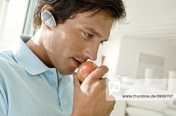 Close-up of a young man wearing a hands free device and eating an apple