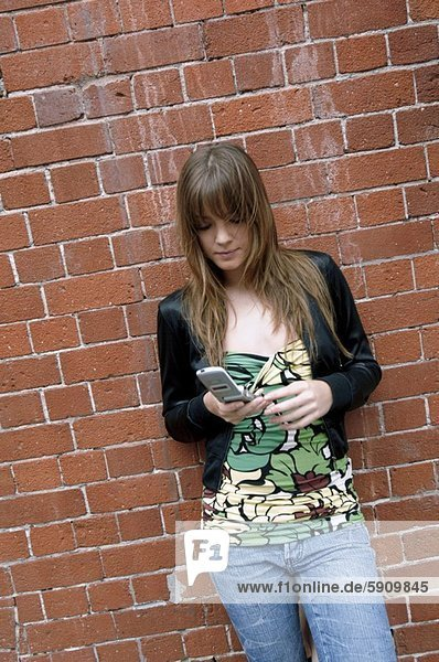 Young woman text messaging with a mobile phone