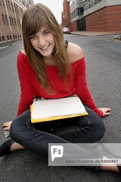 Portrait of a young woman sitting on the road and smiling
