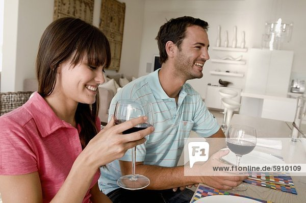 Mid adult couple sitting and holding wine glasses