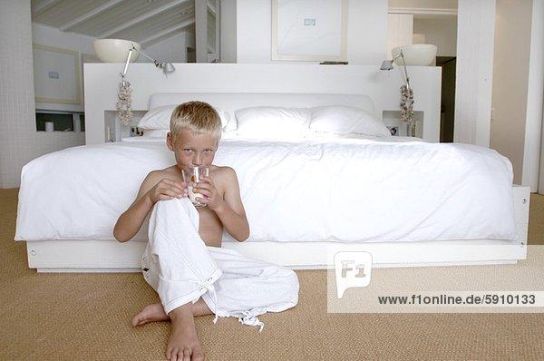 sitzend  Portrait  Boden  Fußboden  Fußböden  Junge - Person  trinken  Milch