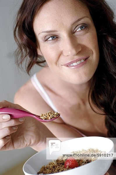 Close-up of a mid adult woman eating cereals and smiling